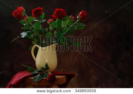 A Moody Photo Of Red Roses In A Yellow Vase.