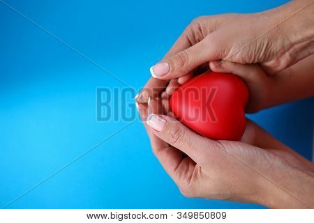 Maternal Care For Health Child, Heart In Hands. Close-up Mother Hands Holding Small Heart And Hands