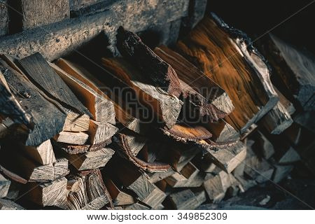 Firewood Is Stacked In A Woodpile In An Old Rustic Barn. Preparing For The Winter And The Heating Se