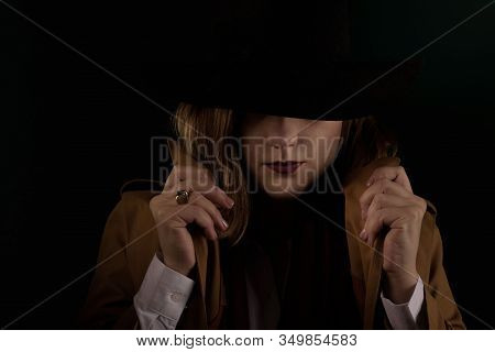 Retro Gangster Woman In A Brown Cloak And Black Hat. Photoshoot In The Style Of The Mafia. Dark Blur