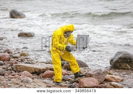 professional in protective coveralls with mini lab on contaminated rocky sea shore