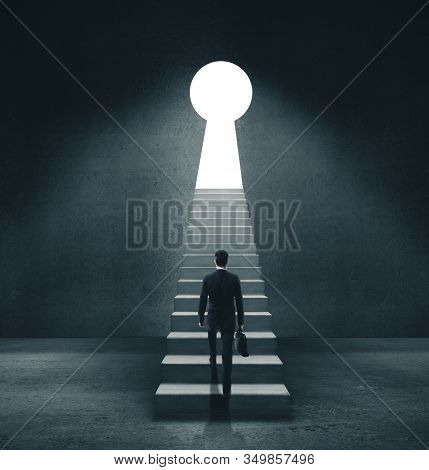 Businessman In Concrete Room Walking To Open Door In Form Keyhole. Motivation And Startup Concept.