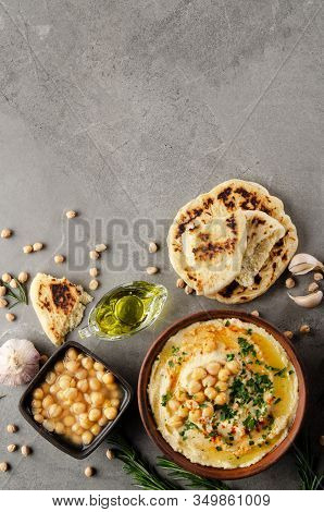 Flat Lay View At Hummus In Clay Dish Topped With Olive Oil, Chickpeas And Green Coriander Leaves On