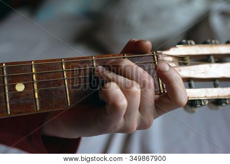 Guy Plays A Melody On An Acoustic Guitar While Holding His Hand On The Fretboard.