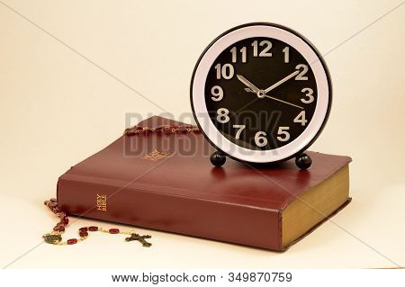 A Clock And Holy Bible Come Together Over A Warm Pink Background To Give Meaning To Various Times An