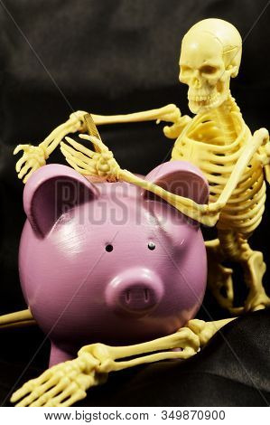 A Skeleton Guards His Piggy Bank While Representing His Scarcity Of Money And Weath.