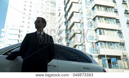 Bodyguard Standing Near Business Car, Checking Safety And Security, Bottom View