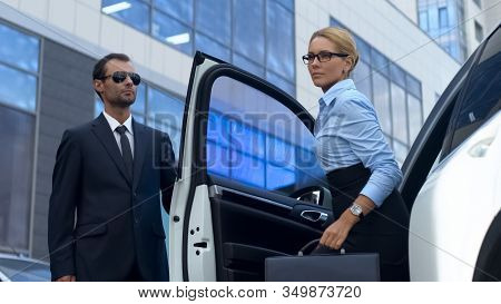 Bodyguard In Suit Opening Car Door To Female Boss, Luxury Service, Success