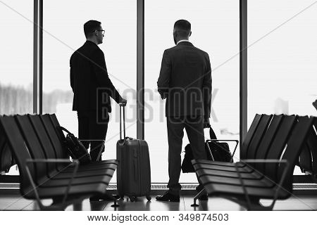 Silhouette Of Two Businessman Standing In Front Of A Big Window At Airport At Wating Area Near Depar