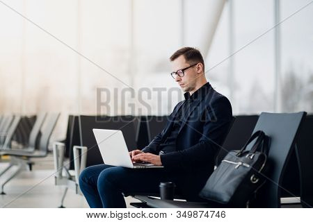 A Business Man Sitting At The Airport Park Working With His Laptop And Drinking Takeaway Coffee Whil