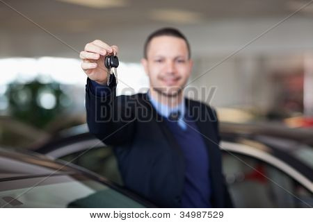 Dealer standing while holding car keys in a dealership