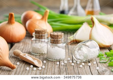 Bottles Of Homeopathic Globules, Onion Bulbs And Fresh Green Onions. Allium Cepa Homeopathic Remedie