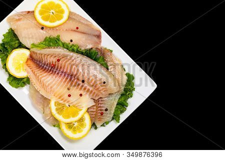 Whitefish Tilapia Fish Raw Fillet Isolated On Black Background. Selective Focus.