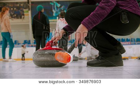 Curling Training - A Granite Stone With Red Handle - A Person Standing Near And Holding A Curling Br