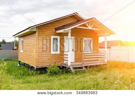 Small Tiny Wooden Frame House With Sundeck And White Windows And Door As A Country Residence In Sunn