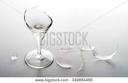 Broken Crystal Wine Glass And Shattered Glass On A Light Background. Selective Focus.