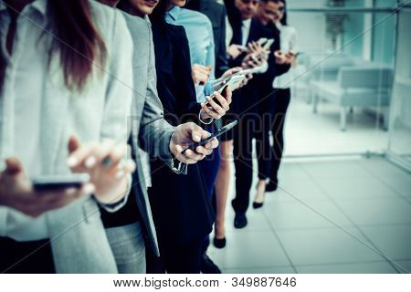 Group Of Young Business People Looking At Their Smartphone Screens