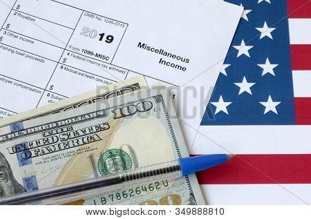 Form 1099-misc Miscellaneous Income And Blue Pen With Dollar Bills Lies On United States Flag. Inter