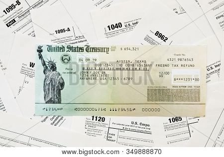 Refund Check On Many Tax Form Blanks Lies On Table Close Up. Tax Payers Paperwork Routine And Bureau