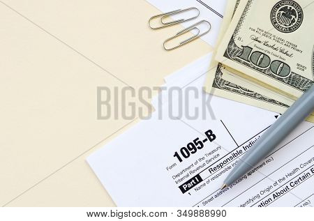 Irs Form 1095-b Health Coverage Tax Blank Lies With Pen And Many Hundred Dollar Bills On Calendar Pa
