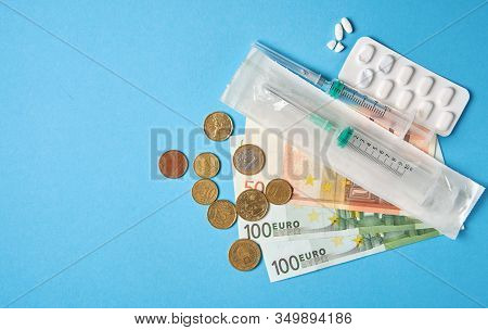 Pills Empty Blisters For Drugs Individual Syringe And Money Lie On A Blue Background Expensive Medic