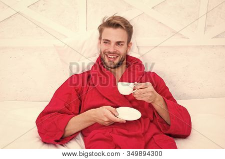Drinking Coffee For Breakfast. Happy Guy Drinking Coffee In Bed. Bearded Man In Bathrobe Holding Dri