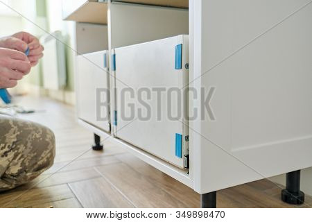 Closeup Process Of Assembling Kitchen Furniture, Hands Of Male Worker. Working Hands Of Male Carpent