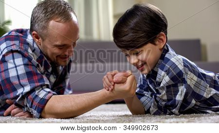 Cheerful Father And Son Arm-wrestling On Floor, Having Fun Together, Rival