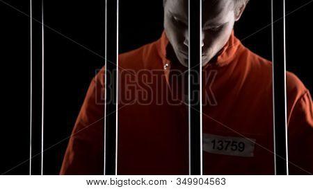 Upset Arrested Man In Orange Suit Behind Prison Bars, Death Penalty Judgment