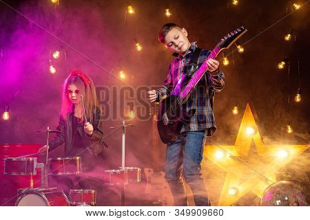Kids Pretending To Be In A Rock Band And Play And Sing At Studio Or Stage. Boy Play On Guitar And Gi