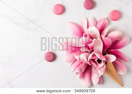 Spring Pink Magnolia Flowers In Waffle Cone With Macaroons On White Background. Spring Concept. Flat