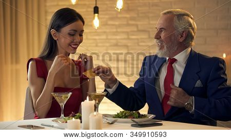 Generous Mature Oligarch Giving Gold Card To Young Girlfriend Sitting Restaurant