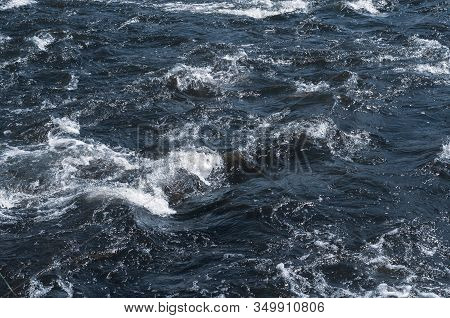 Rapidly Flowing River With Dark Blue Water, Foam. Rapids River Flow, Sparkling In Sun. Photo And Tex