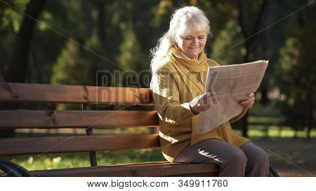 Concentrated Mature Woman Reading Newspaper Sitting On Bench In Park, Retirement