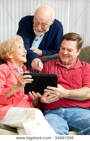 Senior couple learns how to use their new tablet PC from their adult son.