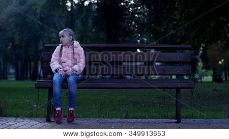 Sad School Girl Sitting On Bench In Park, Lost Missing Kid, Waiting For Parents