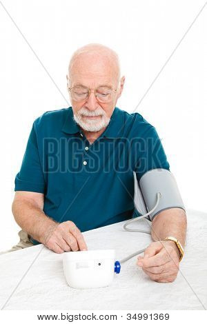 Senior man using a home blood pressure machine to check his vital statistics.  White background.