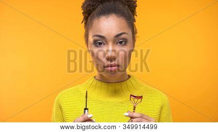 Young Afro-american Female Holding Mascara Brush And Eyelash Curler, Cosmetics
