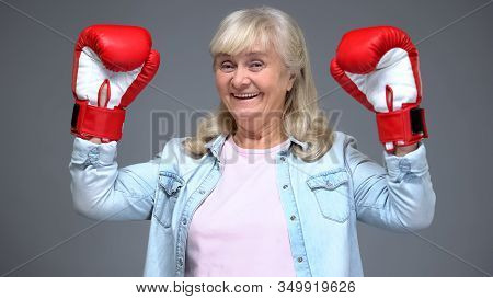 Positive Retiree Woman In Boxing Gloves Rising Hands Up, Success Concept, Belief