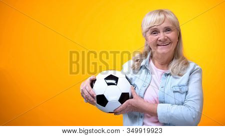 Cheerful Retiree Woman Holding Football Ball, Sports Betting, Positive Attitude