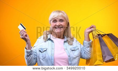 Joyful Aged Woman Showing Shopping Bags And Bank Card, Services For Retirees