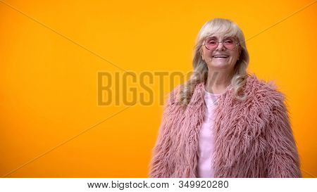 Cheerful Retiree Lady In Funny Pink Coat And Round Sunglasses Posing On Camera