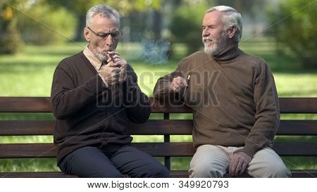 Two Senior Buddies Lighting Cigars, Resting On Park Bench Together, Weekend