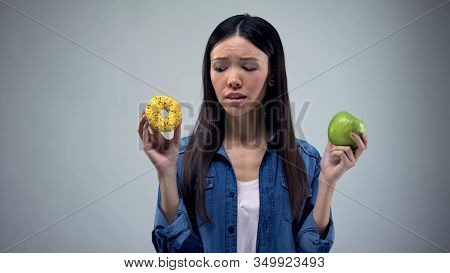 Asian Female Choosing Between Sweet Greasy Donut And Juicy Green Apple, Decision