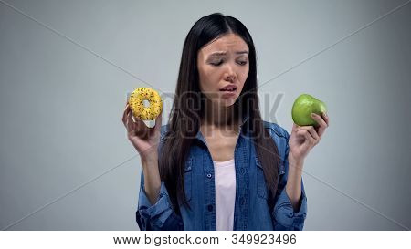 Asian Woman Holding Sweet Greasy Donut And Juicy Green Apple In Hands, Decision
