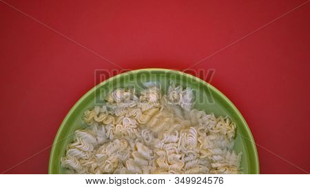 Green Plate With Instant Noodles Soaking In Water On Red Background, Junk Food
