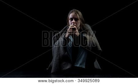 Hopeless Miserable Homeless Woman Eating Bread Sitting In Darkness, Abuse Victim