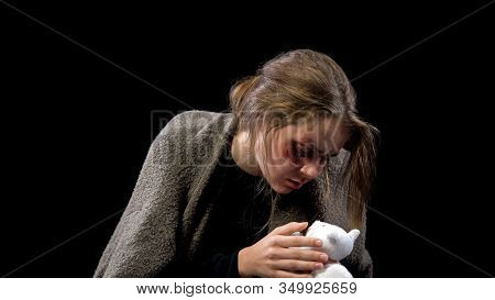 Sad Female With Wound On Face Holding Toy In Hands, Kidnapping Hopelessness