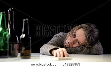 Addicted Weak-willed Woman Lying On Table Near Bottles Of Alcohol, Hopelessness