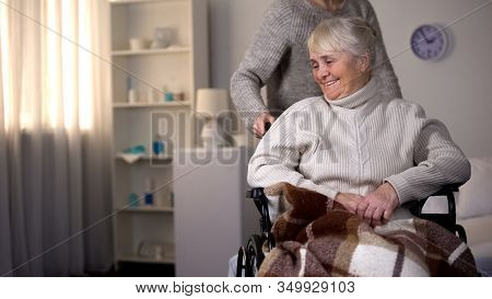 Daughter Taking Care Of Elderly Mother In Wheelchair, Caregiver Helping Patient